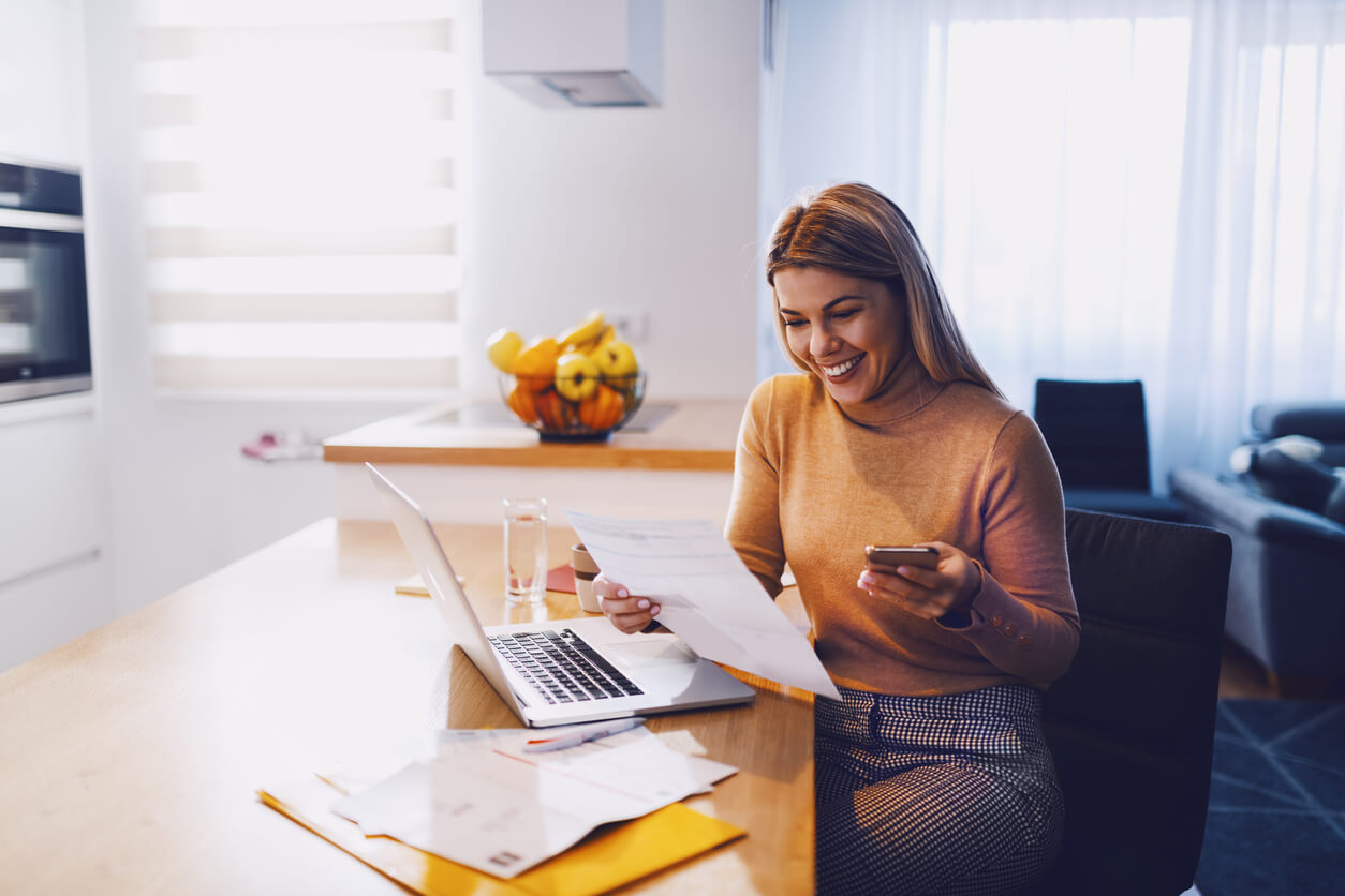 blonde woman looking at papers and laptop smiling